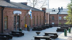 Låg röd tegelbyggnad med texten soldathem, utanför vajar Finlands flagga. Det finns bänkar och bord utanför.