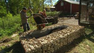 Elin och Owe fyller en odlingslåda med jord