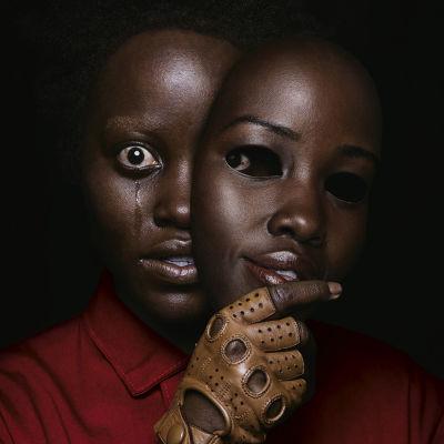 En svart kvinna med skräckslagen blick täcker halva ansiktet med en mask.