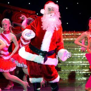 Julgubben på en scen tillsammans med unga dansande damer.