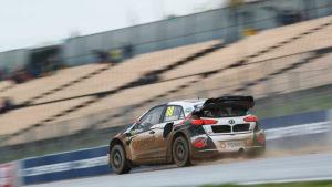 En rallycrossbil åker i hög fart på banan.