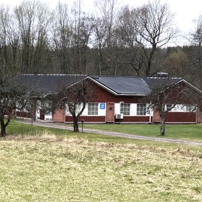Ett rött hus med vitt runt fönstren och svart tak, det är Jehovas vittnes sal i Billnäs.