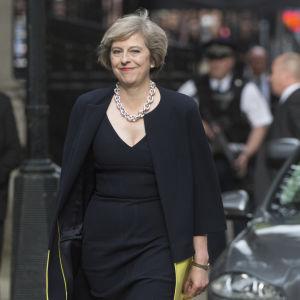 Storbritanniens nya premiärminister Theresa May anländer till 10 Downing Street i silversmycke ler mot kameran.