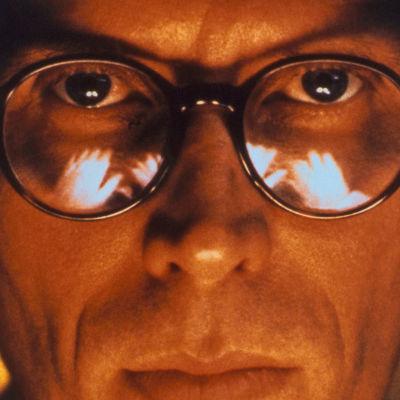 Silmälasipäinen mies (Peter Weller) katsoo suoraan kohti erikoislähikuvassa. Kuva elokuvasta Alaston lounas