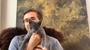 Robin Stethem syns på en skärmdump från ett videosamtal. Han håller upp sin gråa katt Max framför kameran. I bakgrunden syns en gulgrön abstrakt målning. Bildern är lite suddig.