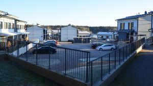Utsikt ner mot en gårdsplan mellan två våningshus. Flera bilar är parkerade på gården.