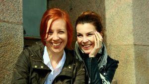 Tutkijat Rose-Marie Peake ja Riikka-Maria Pöllä istuvat Helsingin yliopiston portailla