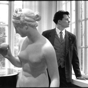 Harri Henttinen mallina. Kuvassa Harri Henttinen katso taka-alalla ikkunasta ulos. Hänen etualallaan on valkoine patsas, joka puolestaan katsoo toiseen suuntaan.