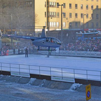 Helikopteri laskeutuu Lahden torille luistinradalle.