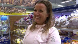 En kvinna som ler framför en bröddisk i en matbutik.