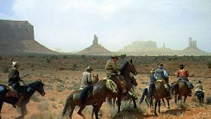 Ratsastajia Monument Valleyssä. Kuva John Fordin lännenelokuvasta Etsijät (1956).