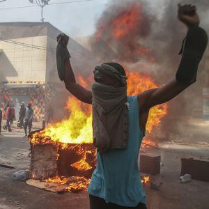 Mielenosoittaja seisoo kädet ylhäällä palavien esineitten edessä Dakarissa.