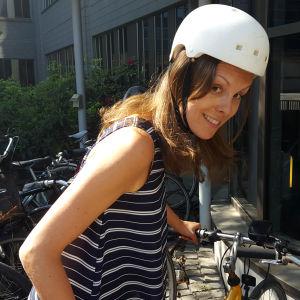 En kvinna parkerar sin cykel.