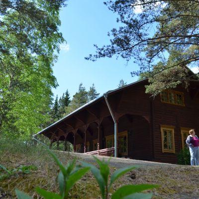 Kolme ihmistä tutkimassa opastaulua suuren punertavan hirsirakennuksen kulmalla vehreässä puistoympäristössä.