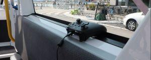 En xbox-kontroller ligger i fönstret på en självkörande buss i Fiskehamnen.