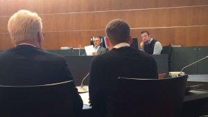 Den åtalade med sin försvarare Kenneth Peth. I bakgrunden domaren Daniel Allén.