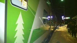 Ett intercitytåg står vid en snöig perrong. Det är mörkt. Mänskor på perrongen.