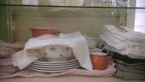 Porslinstallrikar och linneservietter på en hylla.
