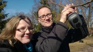 Foneetikko Mietta Lennes ja yliopistonlehtori Toni Laaksonen ripustavat puuhun kaiutinta, jolla testataan suomalaistintin reaktiota tinttijapaniin.