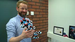 Markus Linder pitää kädessään molekyylimallia.