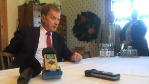 Finlands president sitter vid ett bord.