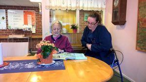 Äldre person och vårdare läser tidning vid ett bord.