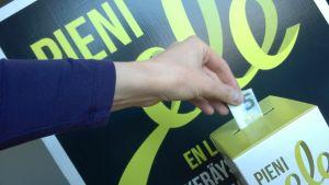 En hand lägger en fem eruso sedel i insamlingslåda