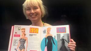 Utställningschef Minerva Keltanen håller i en stor bok om Barbiedockan.