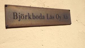 Skylten på kontorsväggen där det står Björkboda lås