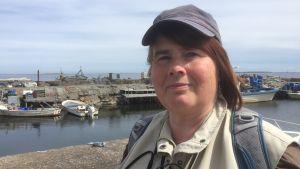 Kvinna står i småbåtshamn och tittar i kameran