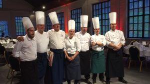Bild på sju krögare som har ordnat en middag. I bakgrunden syns dukade bord.