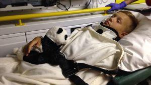 adam nyholm ligger i ambulansen. han har en filt på sig och ett kramdjur i famnen.