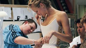 Nuori Alexander McQueen sovittaa mallille vaatetta. Kuva dokumenttielokuvasta McQueen.