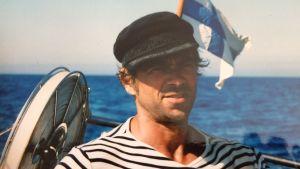 En man står på en segelbåt i randig skjorta och seglarmössa. I bakgrunden finlands flagga och blått hav.