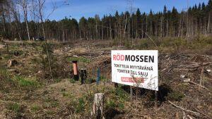 En skylt med texten Rödmossen, tomter till salu på ett uthugget område.