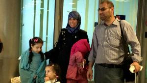 Maher och Wafa och deras två flickor anländer till flygplatsen.