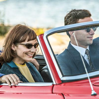 Radio Mercur. Huvudpersonerna Flemming Vestergaard (Andreas Jessen), Anne-Marie Jensen (Neel Rønholt) och Jan Irsinger (Jon Lange) kör röd sportbil.