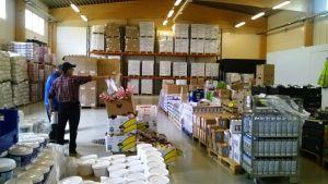 En lagerhall med lådor och varor. Två män står med ryggen till till vänster. Den ena pekar på något i lagret.