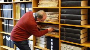 En man i röd tröja håller på med att dra ut eller sätta tillbaka en stor pärm med inbundna dagstidningar på en hylla. I bokhyllan finns också flera andra pärmar.