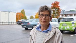 En äldre kvinna i beige jacka står på en parkeringsplats.