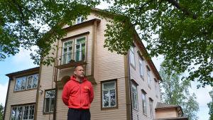 En man i rött står framför ett stort gult hus.