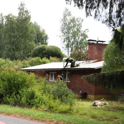 Palomiehiä tulipalossa kärsineen omakotitalon katolla.