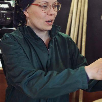 Dokumentaristi Riikka Kaihovaara ottamassa porsasta syliinsä.