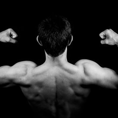 Man med stora ryggmuskler.
