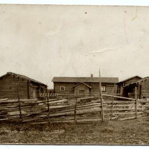 Vanha kuva hirsisen maalaistalon pihasta sauna- ja aittarakennuksineen.
