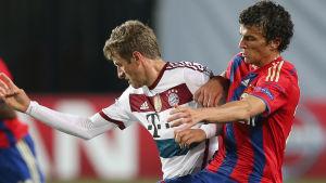 Thomas Müller och Roman Eremenko slåss om bollen.