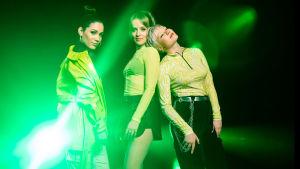 UMK-finalistiyhtye F3M poseeraa vihreiden värivalojen loisteessa. Miara seisoo hieman erillään Baby O:sta ja Vivistä, joka nojaa Baby O:n hartiaan. Kaikilla on päällään neonkeltaista tai -vihreää.