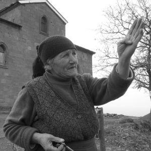 Vanha armenialais nainen kirkon edessä osoittamassa suuntaa kädellään