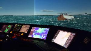 En simulator, i bakgrunden syns ett fartyg som fått slagsida. Längst fram skärmar.