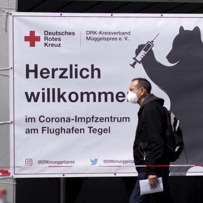 Två män i munskydd går på gatan i Berlin. I bakgrunden syns en reklamskylt för coronavaccin.